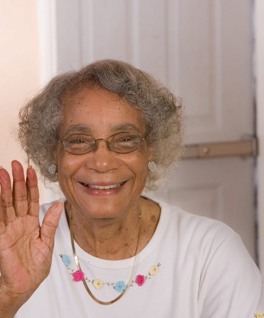 African American senior citizen waving and smiling